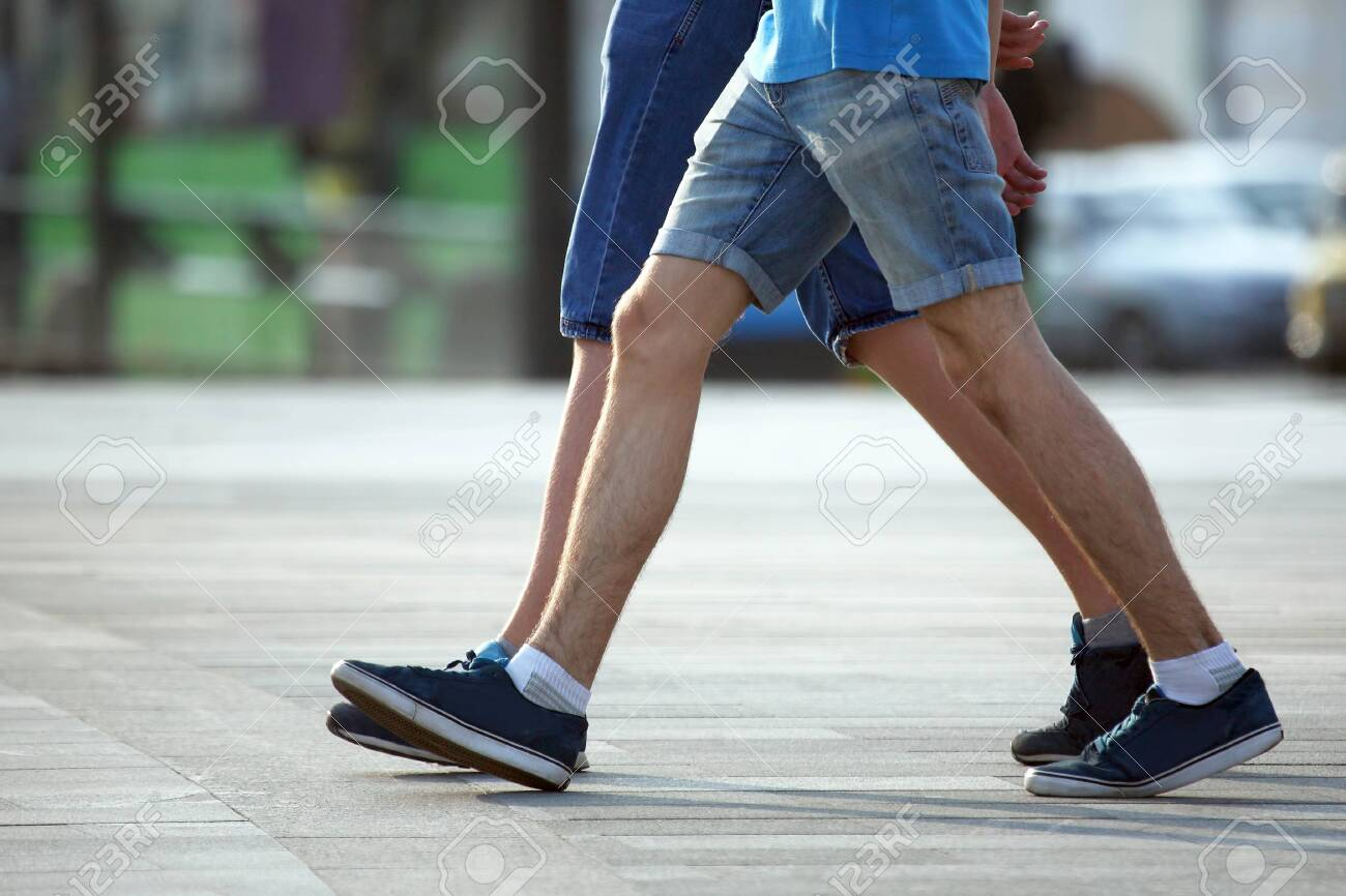 two pairs of feet walking together men